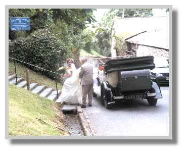 Father helps bride out of wedding car and arranges that special dress - August 2000 photo: R.J.Tarr